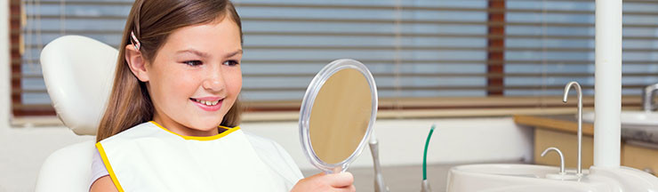 Little girl holding mirror in dentists chair at the dental clini